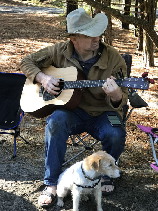 man playing guitar with dog